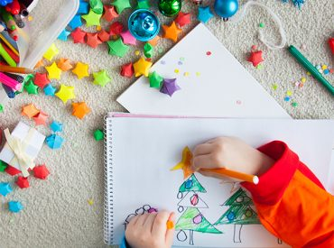 Child's hands drawing a Christmas scene with crafting all around