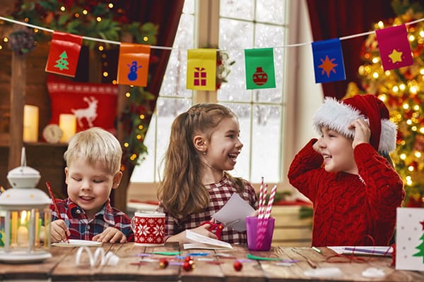 Three children making Christmas crafts
