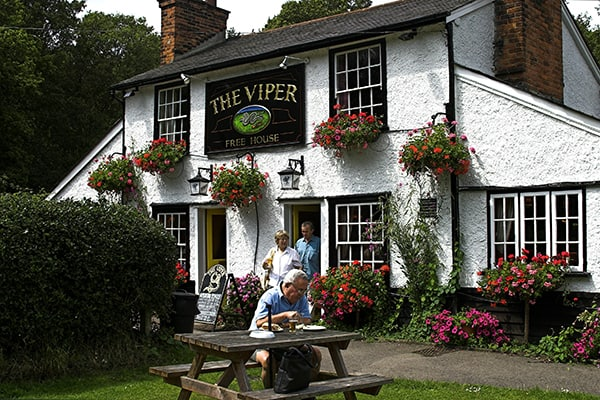 English country pub festooned with hanging baskets in summer. An old man is enjoying a pint and reading his paper on a bench and an old couple happily exit the venue