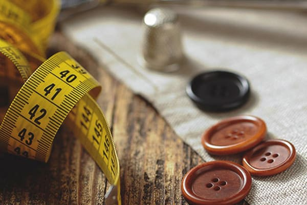 A tailor's tools: tape measure, thimble and buttons