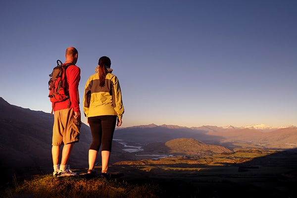 Young couple on a mountain in New Zealand as daybreaks
