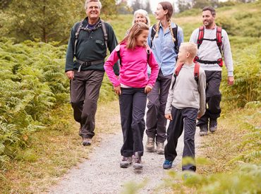 Multi-generational family walking in the countryside together