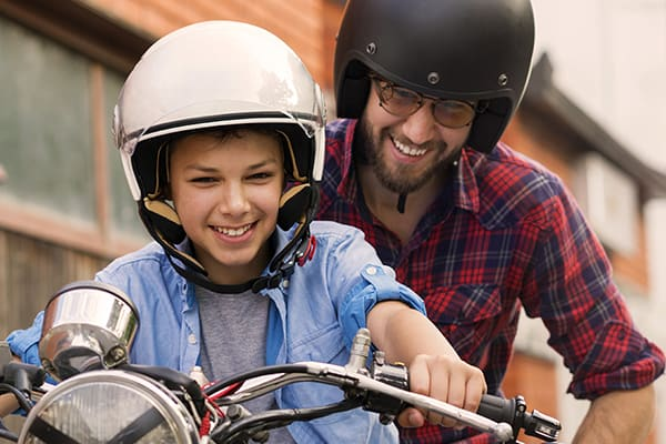 Kid on a bike with dad holding behind, both wearing crash helmets and laughing
