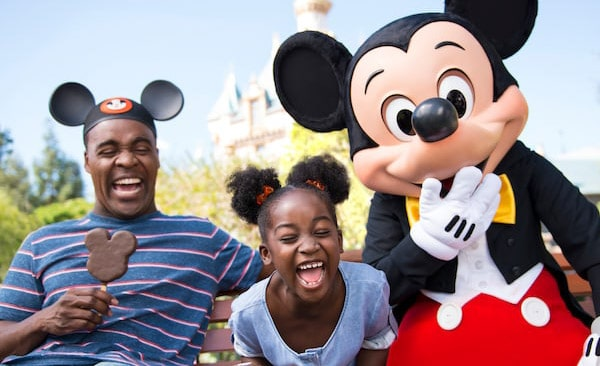 Mickey Mouse laughing to camera with little girl with mouse ear styled hair and dad wearing mouse ear hat
