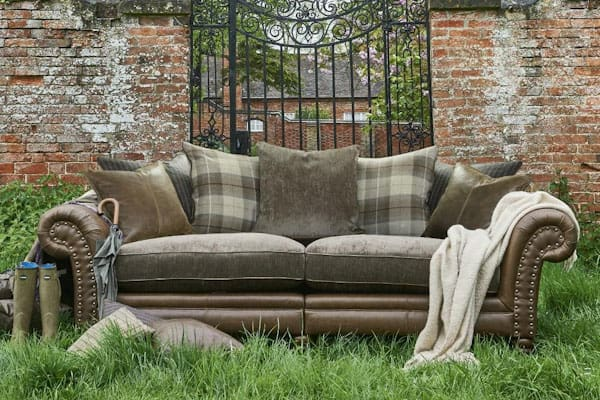 stylish shot of an Alexander & James sofa outside near a garden wall