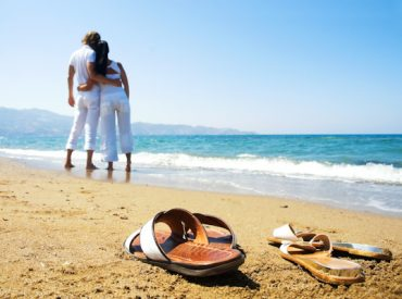 Shoes in foreground of a young couple gazing out to sea on a beach