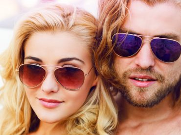 Beautiful couple stare into camera wearing sunglasses and both with golden wavy hair