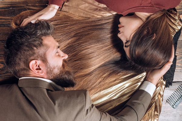 handsome man with beard lays on the long hair of a beautiful woman
