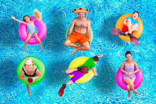 summer fun family posing in the swimming pool with rubber rings