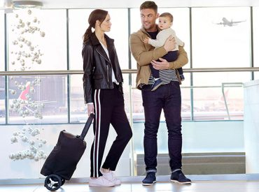 man, woman and baby at airport with stroller
