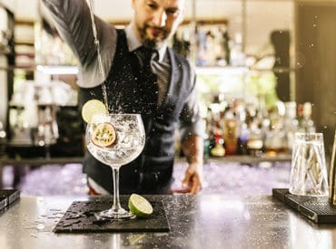 Bartender pouring a cocktail into a glass
