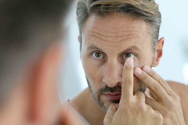 man putting in contact lenses