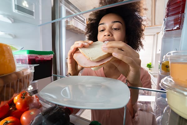 Lady taking a sandwich out of a Samsung fridge freezer