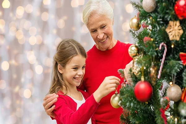 Christmas tree decorating a little girl dressed in red puts bauble on tree while grandma gently smiles and puts her arm around her