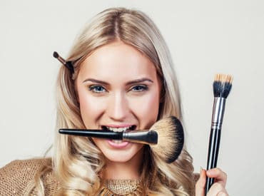 Lady in gold holding up and biting make up brushes