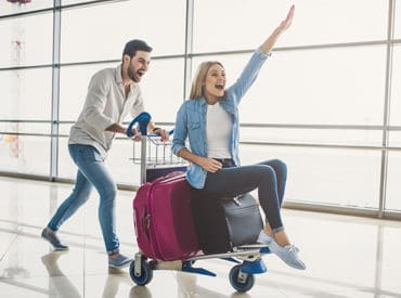 couple with luggage in an airport