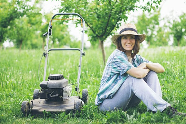 lady in a hat sitting on her lawn smiling next to her lawnmower